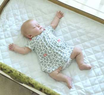 baby sleeping on waterproof portable crib mattress pad