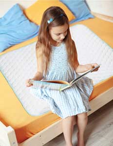 little girl sitting on priva waterproof mattress pad