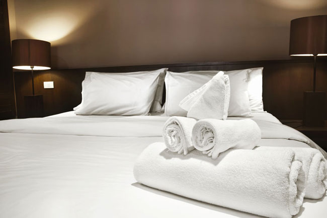 white hotel towels on bed