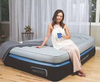 woman sitting on Queen Air Mattress with Headboard AeroBed