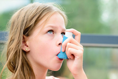 girl using the asthma inhaler