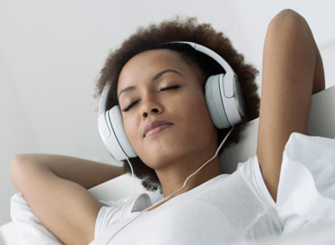 woman relaxing and listening to sleep app sounds