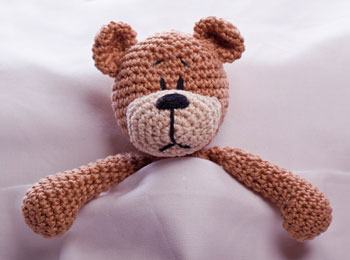 brown teddy bear toy in bed