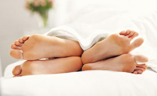 feet of couple back to back sleeping position